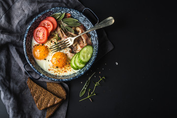Breakfast set. Pan of fried eggs with bacon, fresh tomato, cucumber, sage and bread on dark serving board over black background