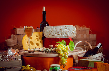 Cheese and wine on a dark table.