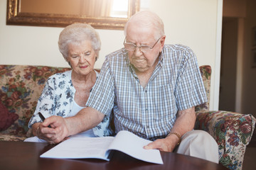 Retired couple looking over documents at home