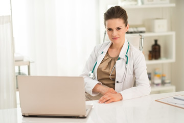 Portrait of female doctor sitting at a desk in the office