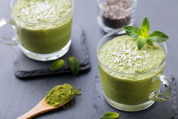Matcha green tea chia seed pudding, dessert with fresh mint and coconut on a black slate background Healthy breakfast