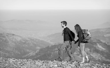 Active couple hikers climbing up with backpacks on the ridge of the mountain, open overview on the mountains on the background. Couple is smiling and holding hands. black and white