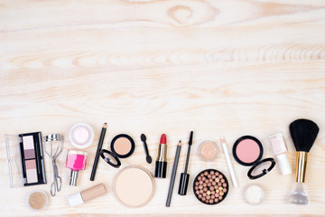 Makeup cosmetics on white, wooden background with plenty of copy space. Top view.