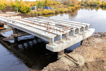 Concrete bridge across Tagil river under-construction of its foundation and road surface supporting structure.