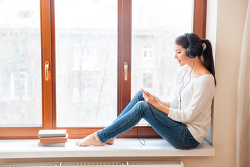 Woman sitting on windowsill and using smartphone with headphones