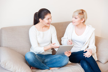 Two women using tablet computer on the sofa