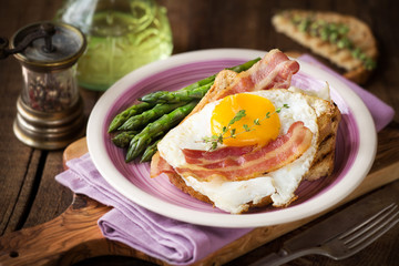 Delicious homemade breakfast with eggs, asparagus stalks, bacon and toast on dark rustic wooden background