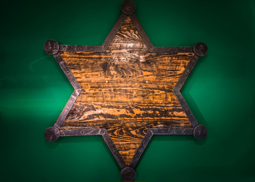 Wooden Sheriff Star on green wall