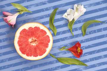 Ripe bright fruit grapefruit with flowers on striped background top view. Striped background in blue and dark blue stripes.