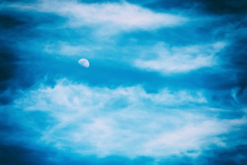Moon Visible In Blue Sky With White Soft Clouds