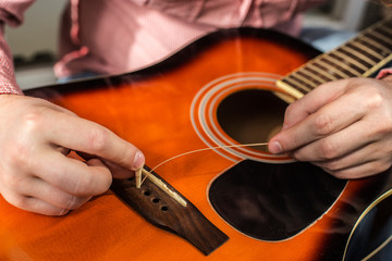 a man changing old ripped guitar strings on the acoustic guitar