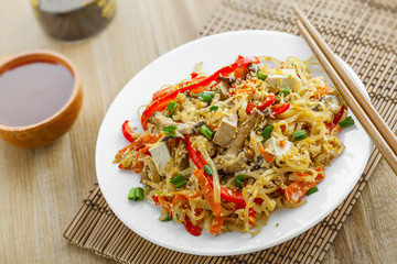 Asian food. Fried rice noodles with tofu, vegetables and shiitake mushroom. Oriental cuisine meal. Close-up.