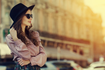 Outdoor portrait of young happy lady posing on street. Model wearing stylish clothes. Girl looking aside. Sunny day. Female fashion. City lifestyle. Toned style instagram filters. Copy space for text