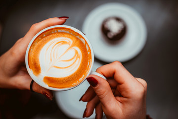 Cup of cappuccino in hands