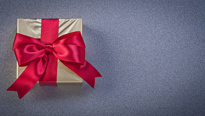 Present box wrapped in glittery paper on grey background holiday