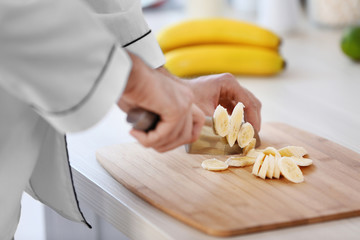 Male hands cutting banana on a wooden board.