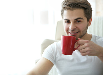 Portrait of young smiling man with red cup of coffee