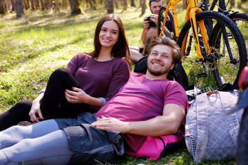 One male and two female relaxing in a park.