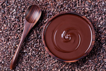 Bowl of melted chocolate and wooden spoon on a crushed raw cocoa beans, nibs background. Copy space Top view