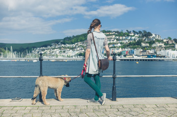 Young woman with Leonberger puppy standing by water