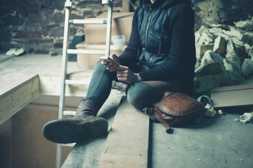 Young woman using cell phone in loft space