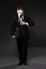 Businessman with money and briefcase posing in full length in studio. Man in black suit wearing mask over grey background.