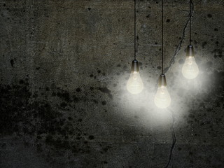 Close-up of three white turned on light bulbs against dark gray concrete wall background