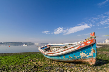 Small, old traditional boat in Seixal bay. Portugal.