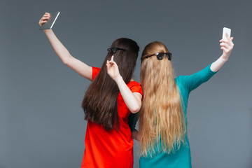 Two women covered face with long hair and taking selfie