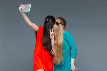 Two comical women with faces covered by hair taking selfie