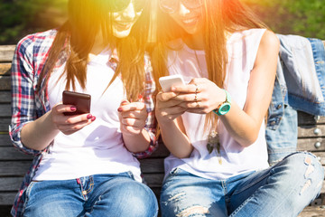 Young happy teenage girls using their phones and having fun in summer park.