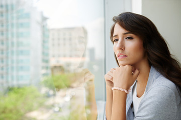 Pensive young woman looking through the window