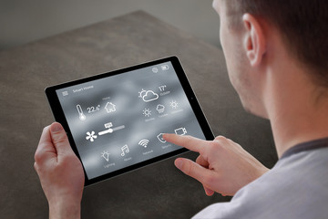 Man use application for smart home control on tablet. Interior of living room in the background.