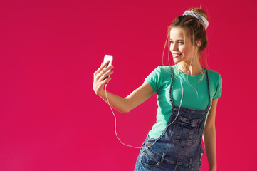 Pretty young blonde woman listening to music in earphones and taking selfie picture with her phone