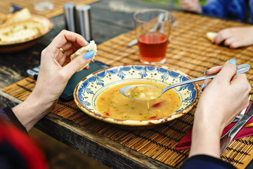 Bean soup in bowl with fresh sliced bread on napkin, on wooden t