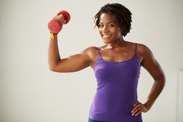 Portrait of fir woman posing with dumbbell
