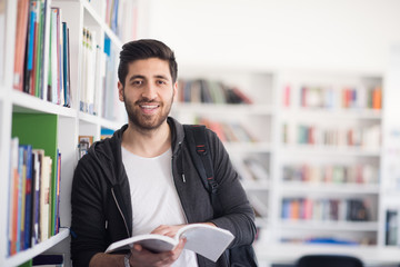 portrait of student while reading book  in school library