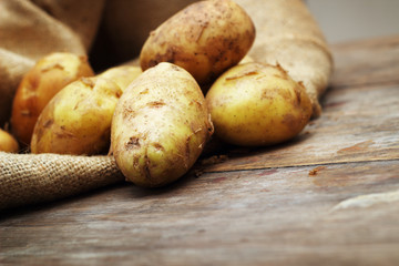 Raw potatoes on wooden background