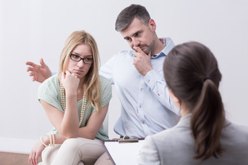 Young married unhappy couple on psychotherapy session