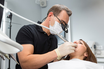 Dentist treating patient on chair with a dental drill
