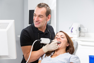 Dentist scanning patient's teeth with a CEREC scanner