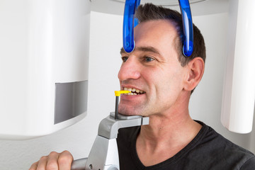 Patient in dentist's panoramic and cephalometric x-ray system