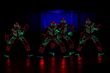 Fototapeten Karneval dancers in led suits on dark background, colored show