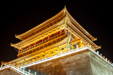 The illuminated ancient Drum Tower located at the ancient city wall by night time, Xian, Shanxi Province, China