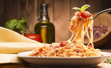 spaghetti with amatriciana sauce in the dish on the wooden table Fotomurales