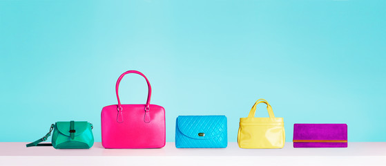 Colorful collections of bags and purses. Isolated on blue background.