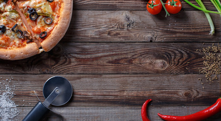 Tasty pizza with ingridients on a wooden board.