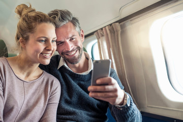 Couple on airplane, looking at smartphone, smiling