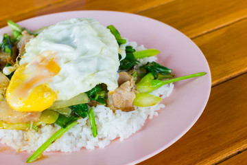 Fried meat with kale and egg with rice on wooden background, copyspace