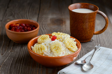 Cottage cheese in color bowl with banana and cherry on wood back